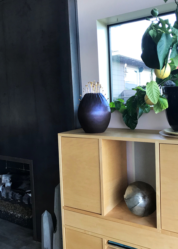 Contemporary metal sculpture displayed on wood built in cabinet with lemon tree next to steel fireplace