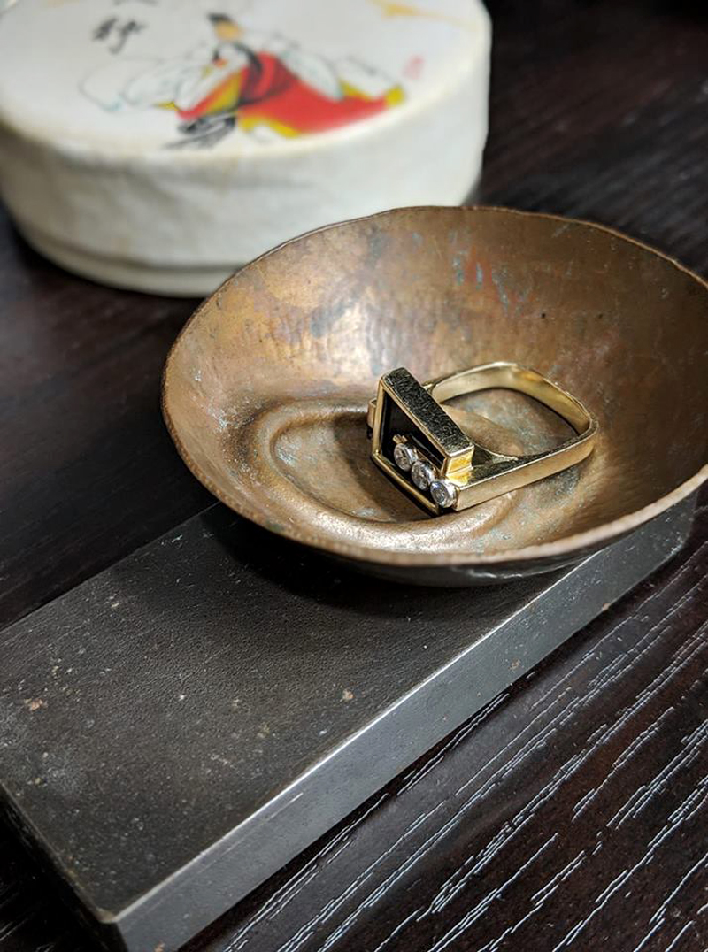 handmade hammered brass ring bowl on wood base containing gold diamond ring on bathroom vanity