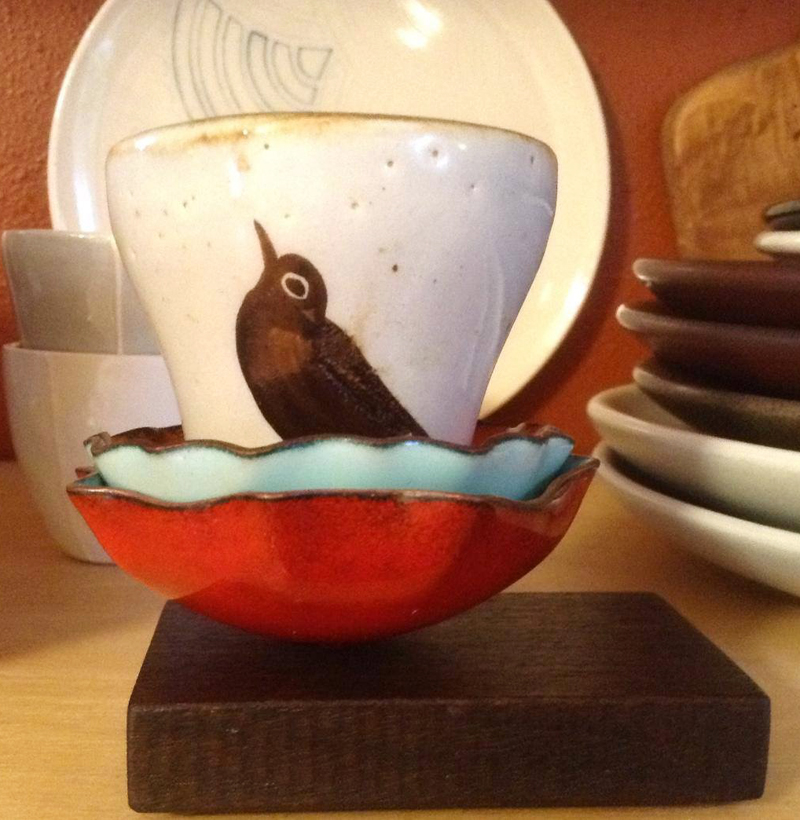 kitchen open shelf display with stacked red blue bowls and nesting bird ceramic cup