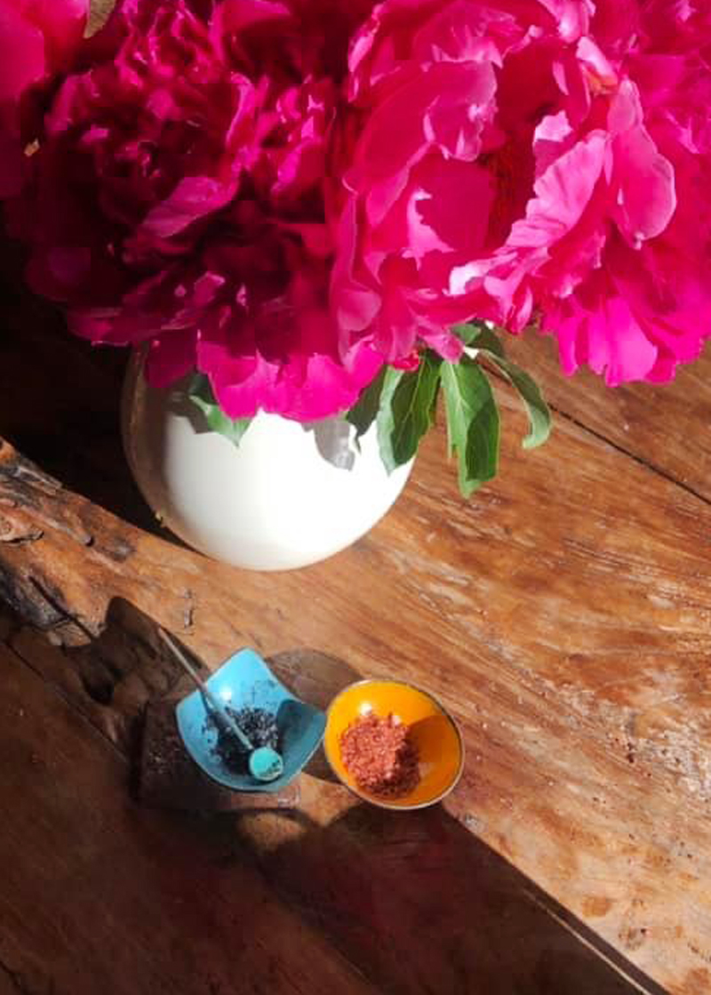 rustic wood kitchen table with pink peonies, blue square bowl and little blue spoon and round orange salt cellar