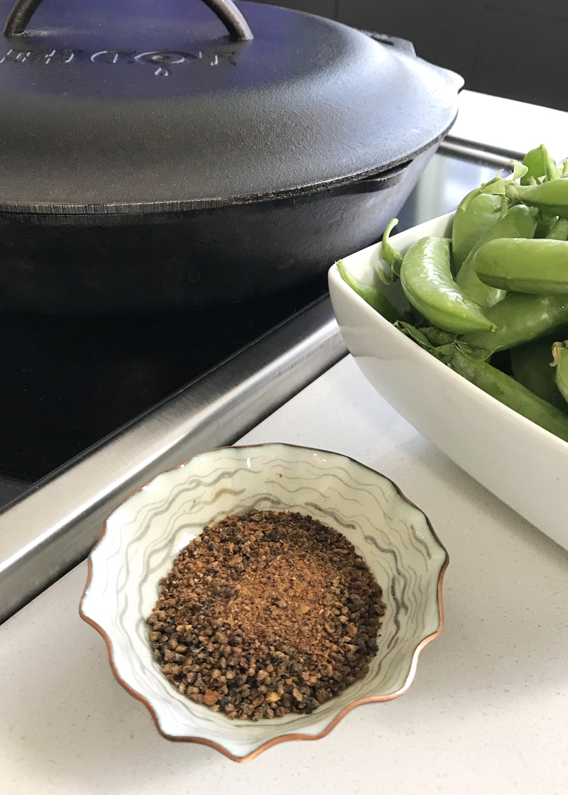 cooking in cast iron, fresh bright sugar snap peas, copper white and black handmade spice bowl with Wren's garlic pepper
