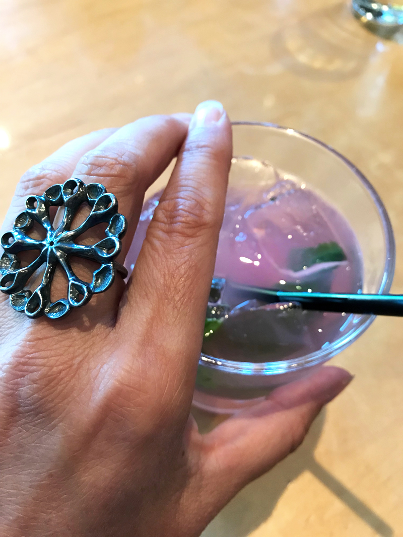 pink cocktail and hand wearing large black silver flower power ring