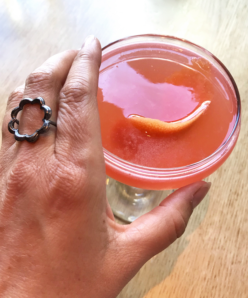 pink gin cocktail with orange twist and black silver scallop circle ring on middle finger holding glass
