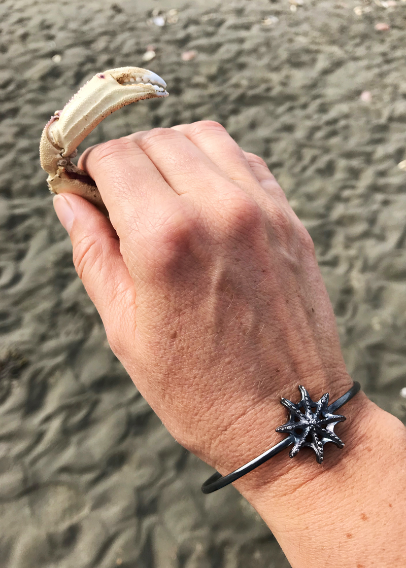 sea star bracelet and intricate crab claw on beach - contemporary nature jewelry design