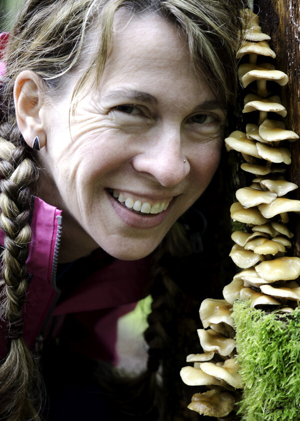 woman wearing dark silver contemporary organic leaf hug earring while forest bathing near mushroom troop on bright green moss covered tree in cascade mountains