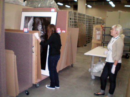 Sarah and Lauren working with the framed photos in the collections area.