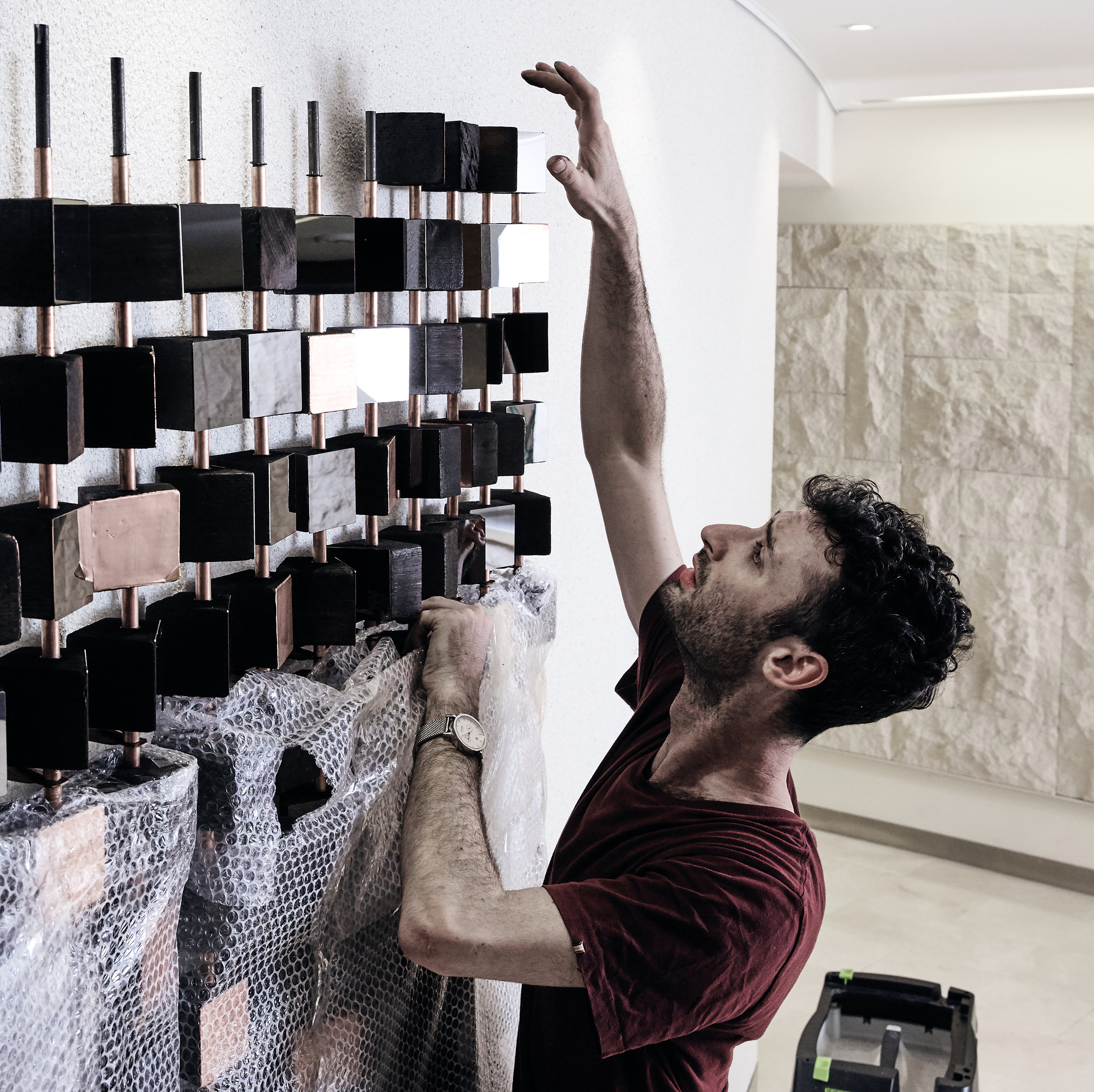 Jonathan, making the final adjustments to the installation at Deloitte. Credit: So Watt/Nic Gossage