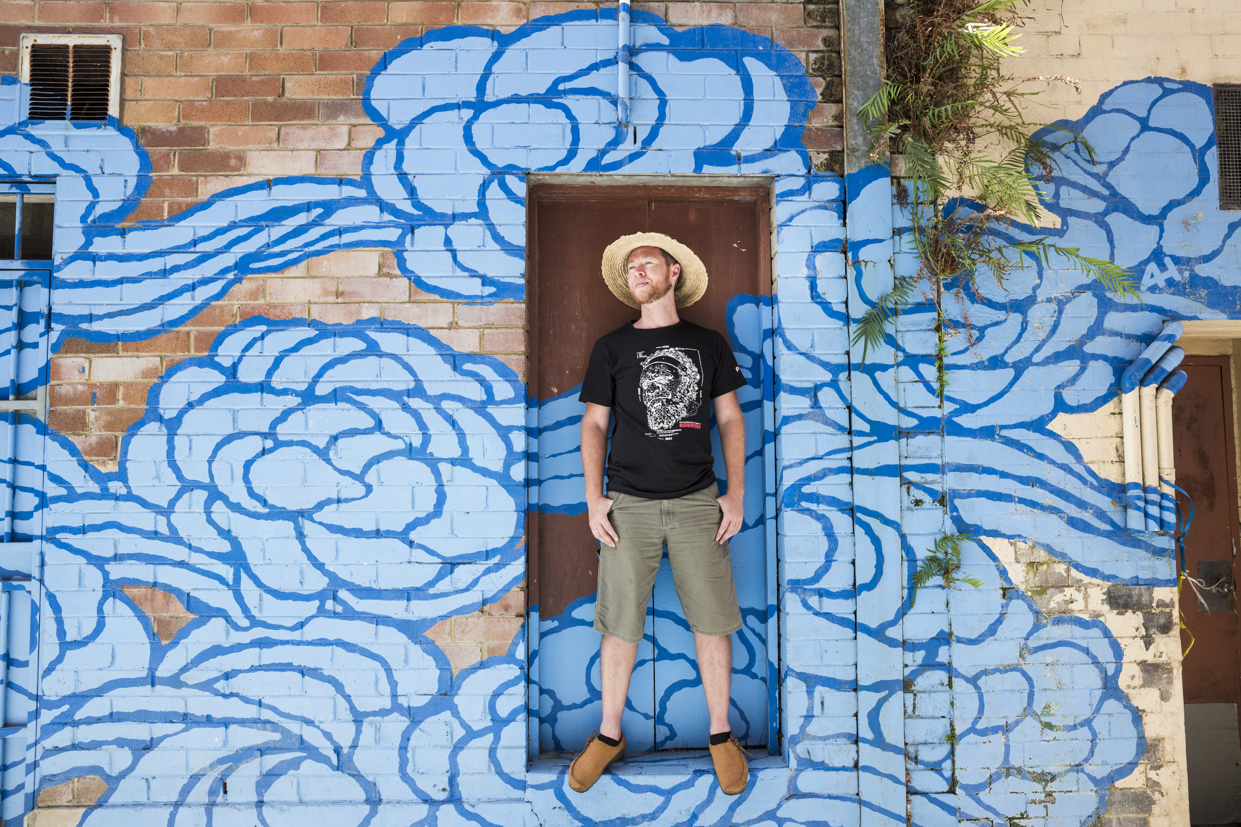 Jason Wing with his mural  Between Two Worlds  by day. Image Credit: Art Pharmacy Consulting.