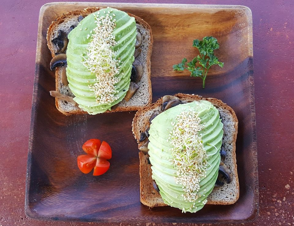 Avocado Toast - Two slices of toasted VIVO bread topped with sautéed mushrooms, local avocado and toasted sesame seeds