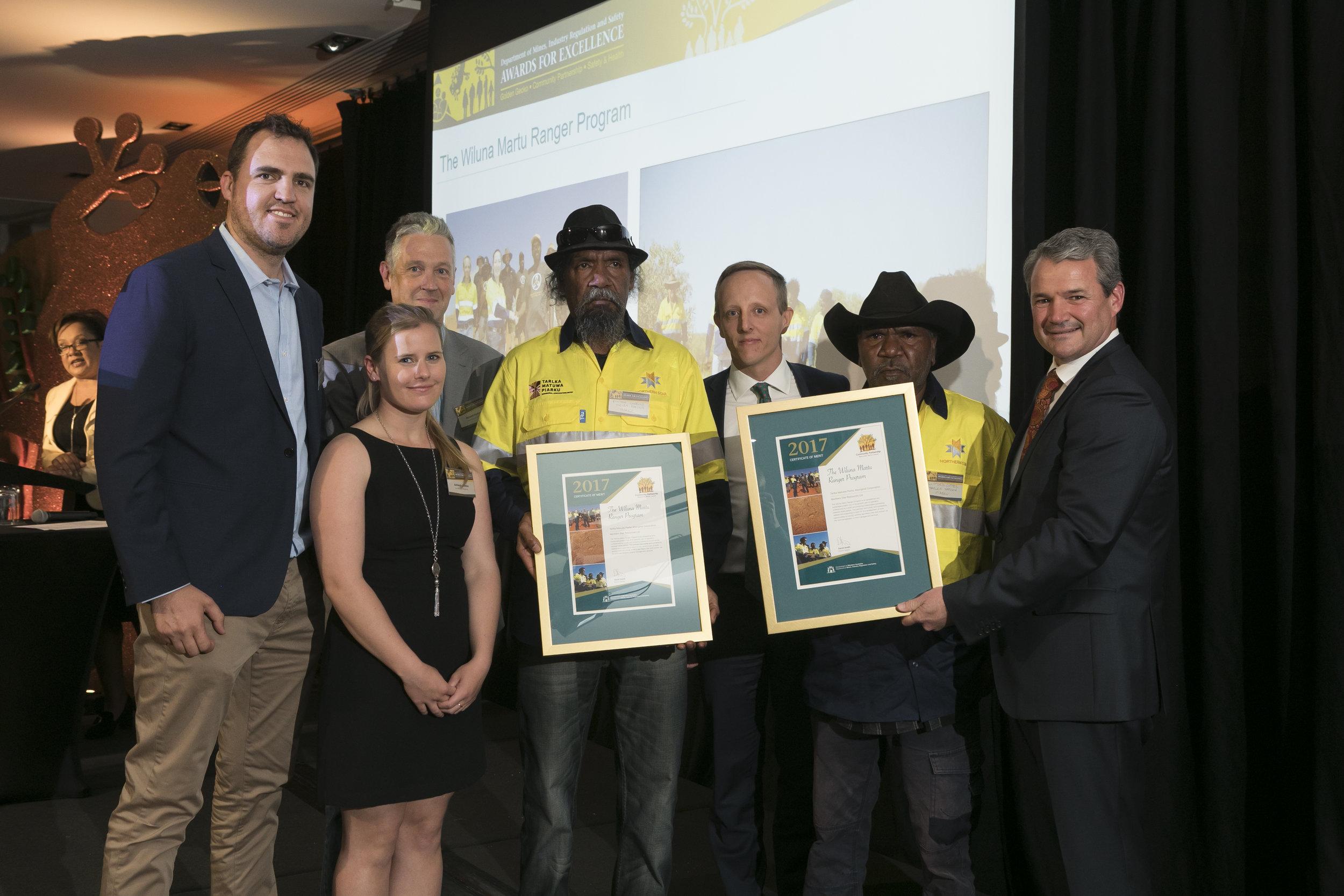 Abraham Van Niekerk, Ashleigh Shelton, Richard Gordine, Ray Carbine, Guy Singleton and Clifford Cutter receiving a Certificate of Merit for the Martu Ranger Program in the 2017 Community Partnership Awards.