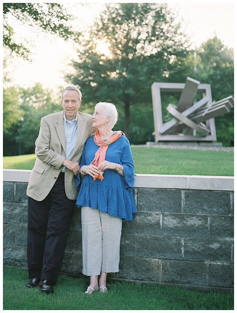 Golden backlight on the couple in front of the sculpture