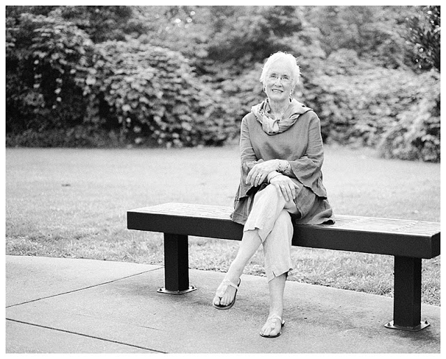 Barbara seated on a bench along the Riverwalk path