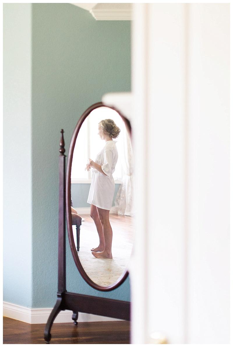 Bride getting ready through antique mirror