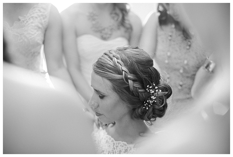 Bridesmaids and family praying over the bride before her wedding