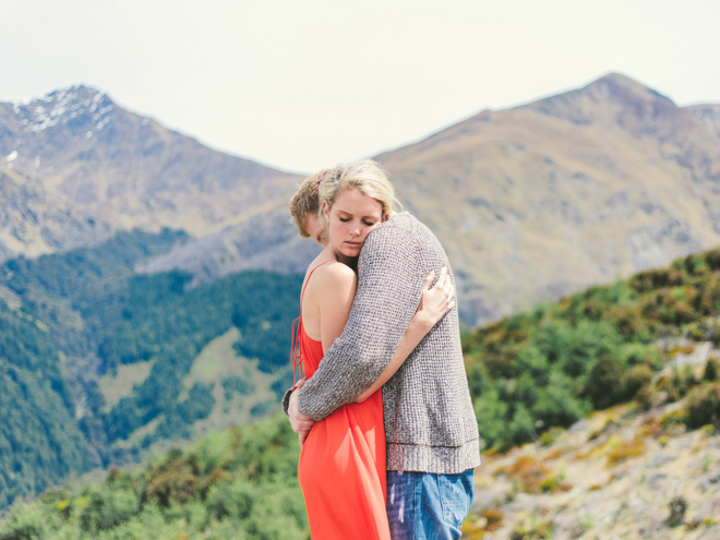 Bride wearing red dress for engagement session on top of the mountains in New Zealand