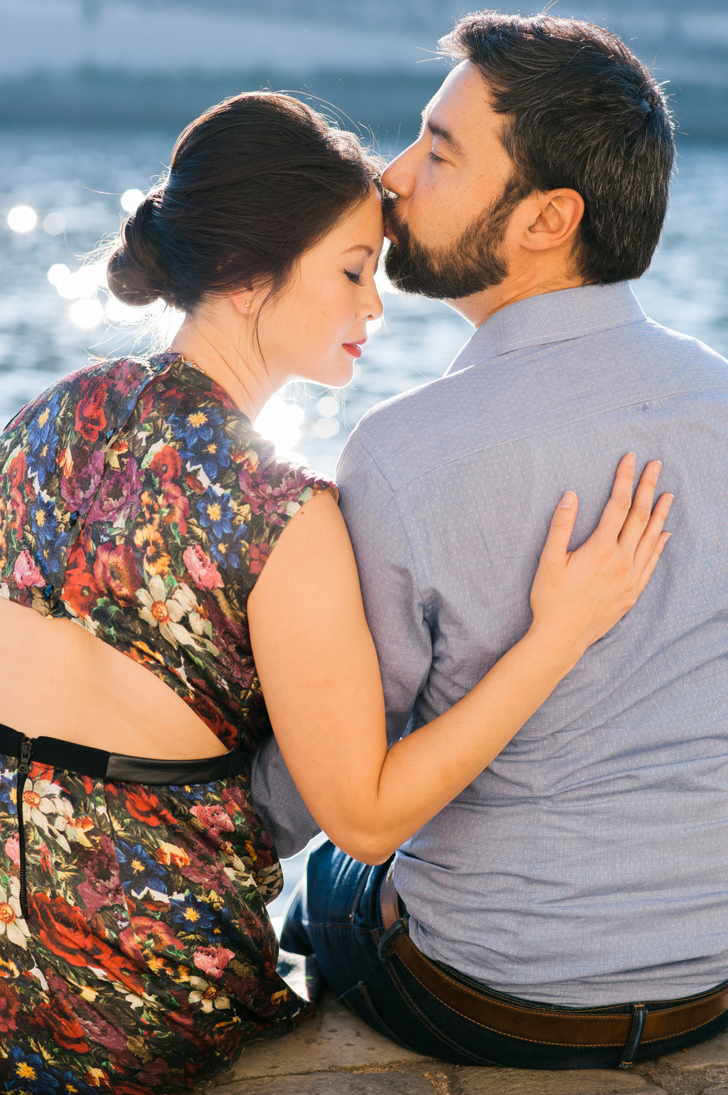 Gentle kiss along river le Seine bride wearing floral bear back dress