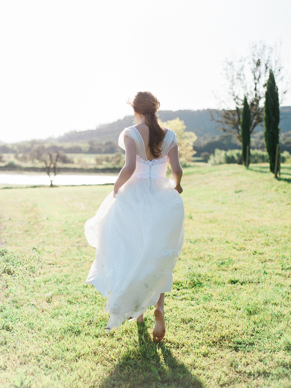 Bride running barefoot in a field wearing Rime Arodaky dress