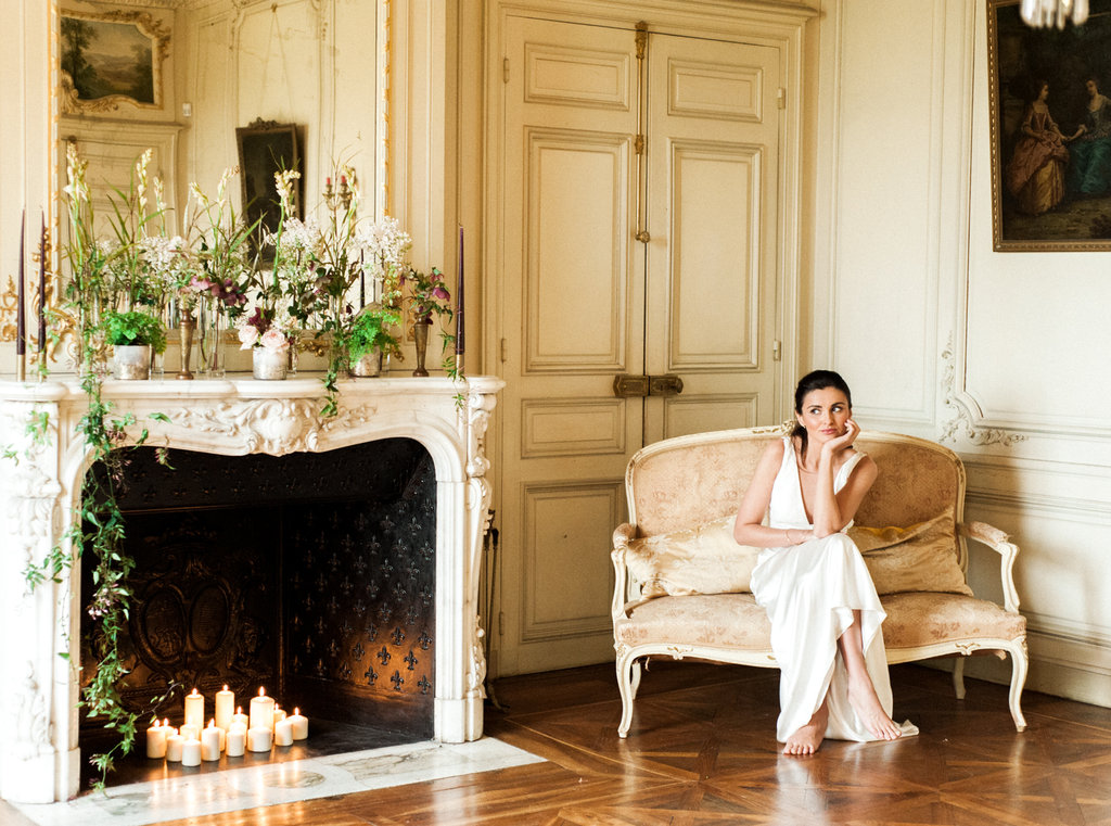 Bride wearing Charlie Brear wedding dress sitting by fireplace