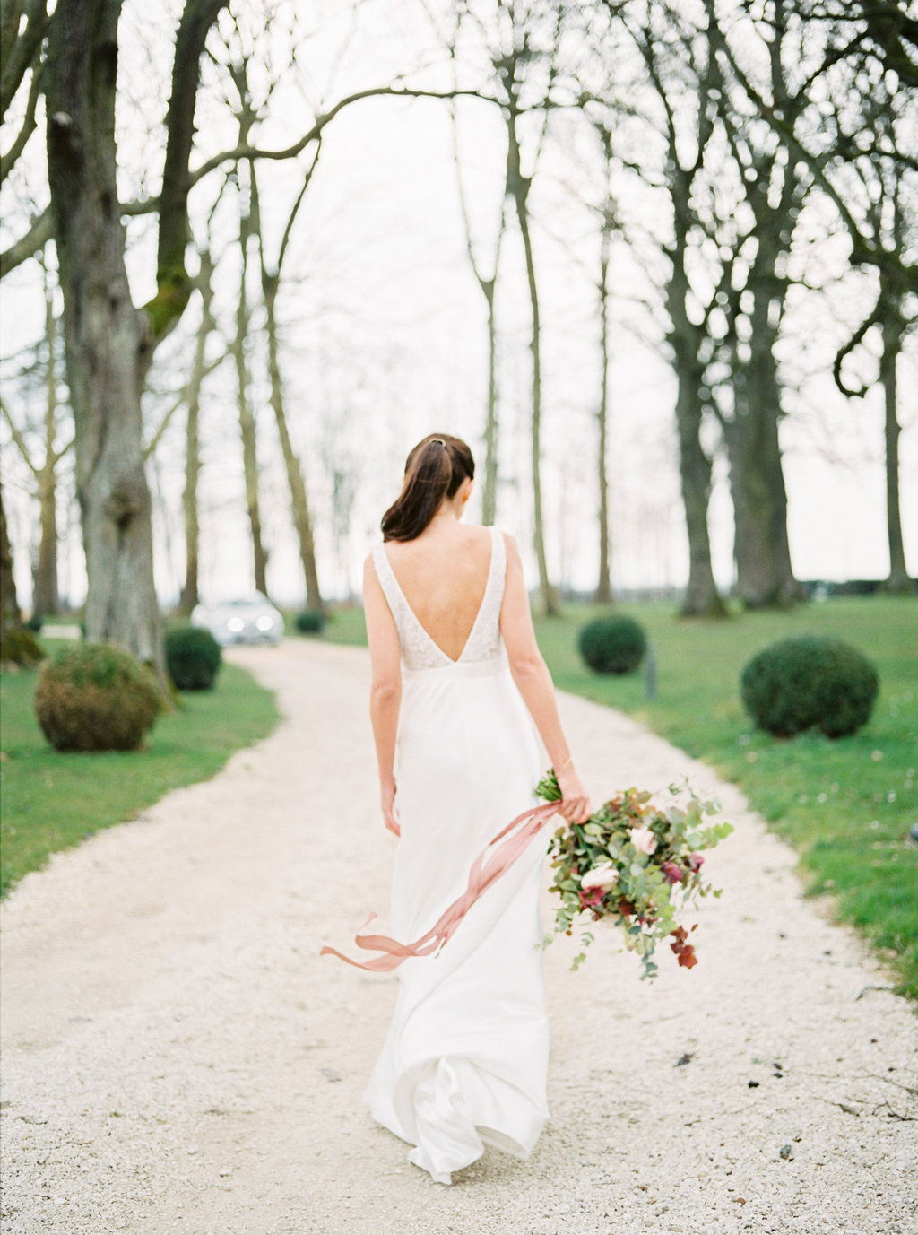 Bride with wedding bouquet and silk ribbons floating in the wind