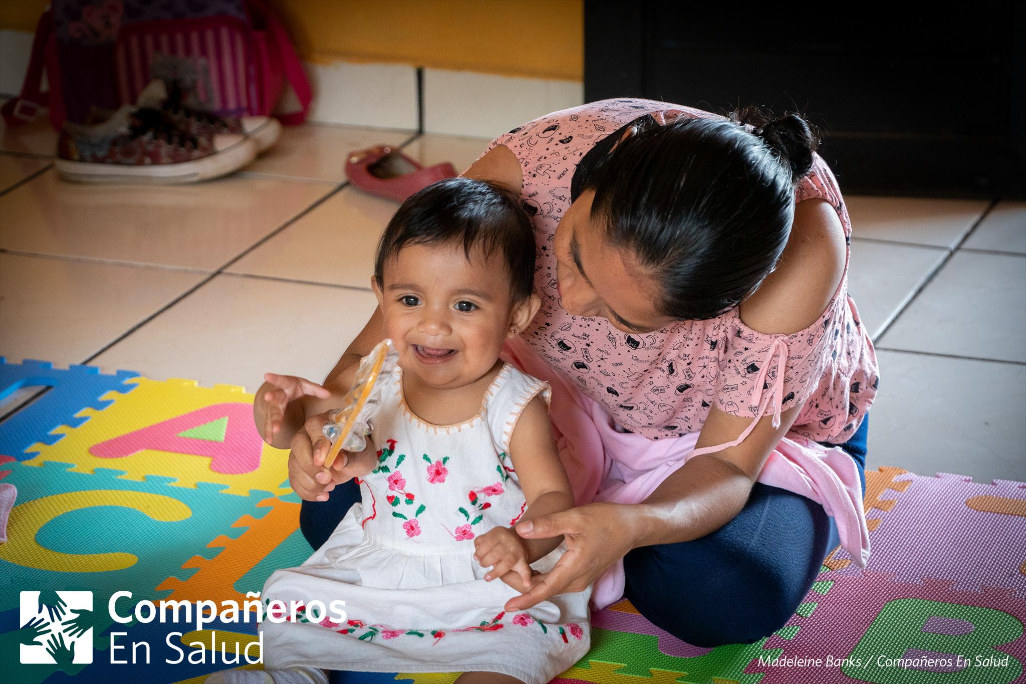 Durante un curso de desarrollo infantil y estimulación temprana en Jaltenango de la Paz, la mamá Verónica Ramírez Torres ayuda a su hija Regina a tocar un pequeño instrumento musical.
