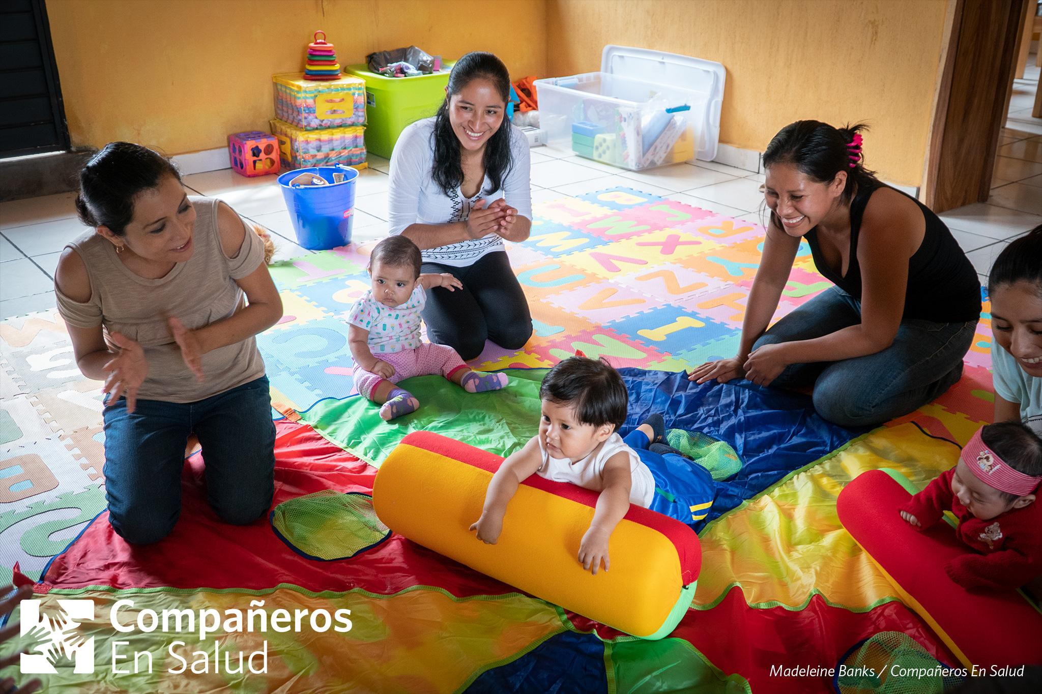 La maestra Luisa Fernanda Estrella Maza y el grupo de madres en el curso de desarrollo infantil y estimulación temprana animan al niño Darek mientras él trata de cruzar el tapete.