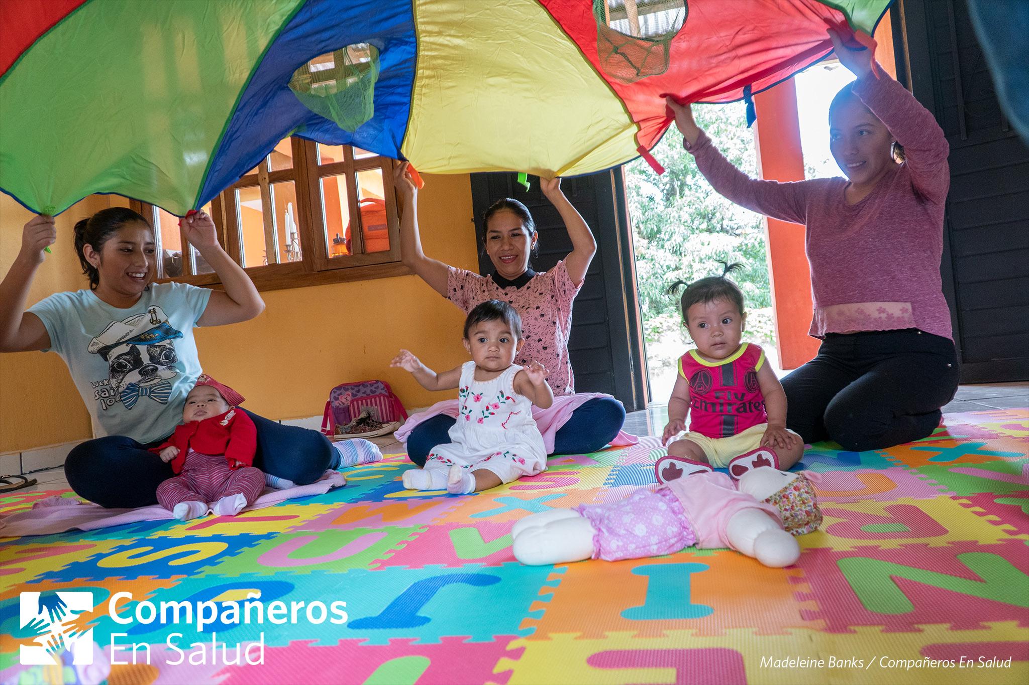 Mamas de Jaltenango de la Paz agitan un paracaídas sobre sus hijas y cantan sobre los colores durante un curso de desarrollo infantil y estimulación temprana.