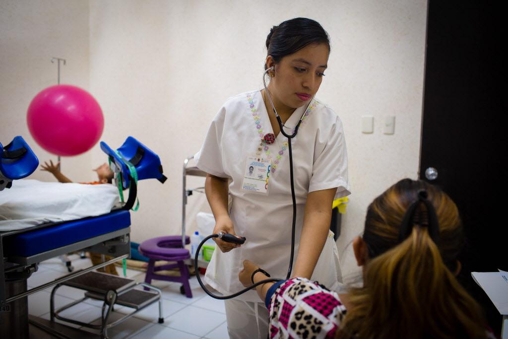 Foto: Alma Rosa Valentin Martinez (centro), una enfermera obstetras realizando su servicio social con Compañeros En Salud en la Casa Materna, toma la presión de Gloriena Elizabeth. Su hijo Ángel (de 4 años), juega con una pelota de partos durante la consulta. (Foto por Cecille Joan Avila / Partners In Health)