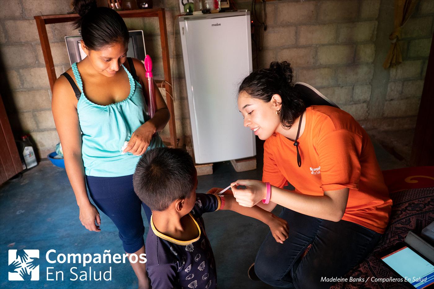 Durante las encuestas para los niños, evaluamos el riesgo que tienen de padecer enfermedades como asma o desnutrición.  Foto: Ana Laura mira mientras Luz Estefanía Güereña Orozco, estudiante de medicina, mide el tamaño del brazo de su hijo Ángel como parte del proceso de evaluar su riesgo de desnutrición.