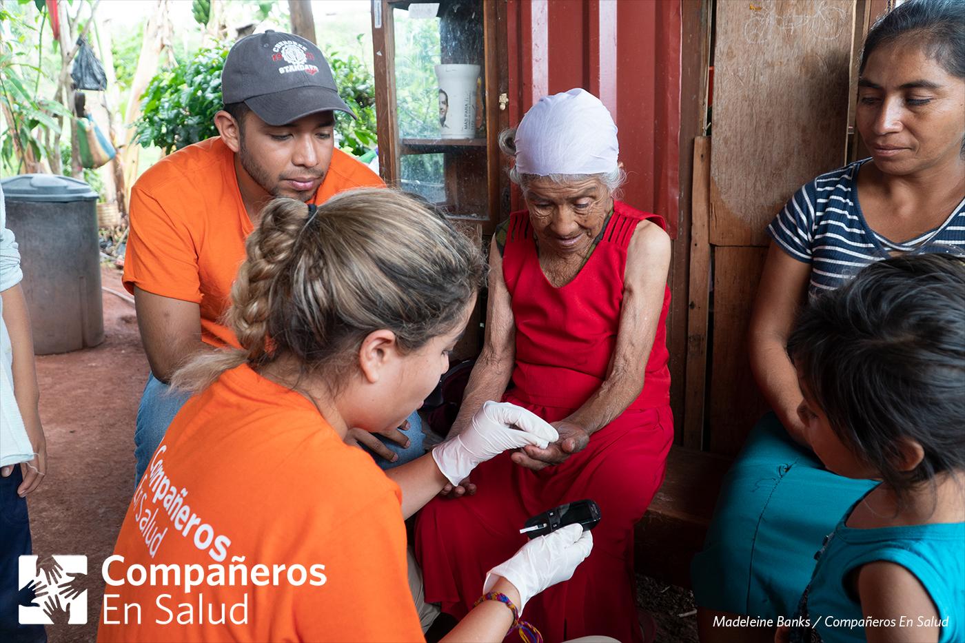 Foto: Gala Limón Saldivar, estudiante de medicina, mide el nivel de glucosa de doña Luisa mientras su hija Rosalinda, su nieta Kenia, y el supervisor clínico de Compañeros En Salud, Argel Martinez, observan.