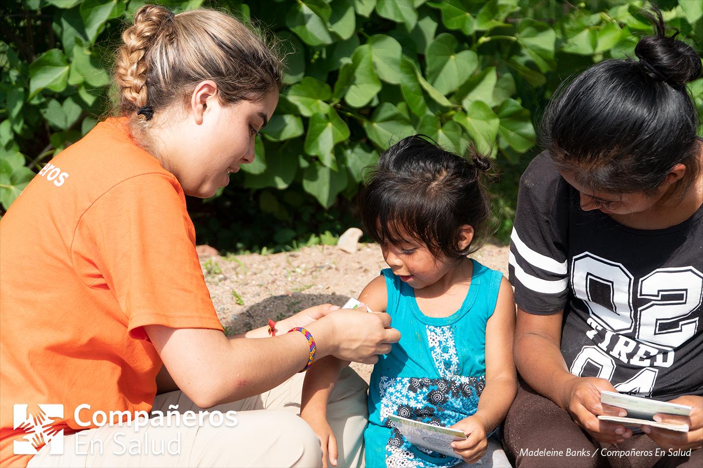 También, nos aseguramos de que sus esquemas de vacunación estén actualizados.  Foto: Doña Araceli proporciona los esquemas de vacunación de sus hijos mientras Gala Limón Saldivar mide el tamaño del brazo de Kenia.