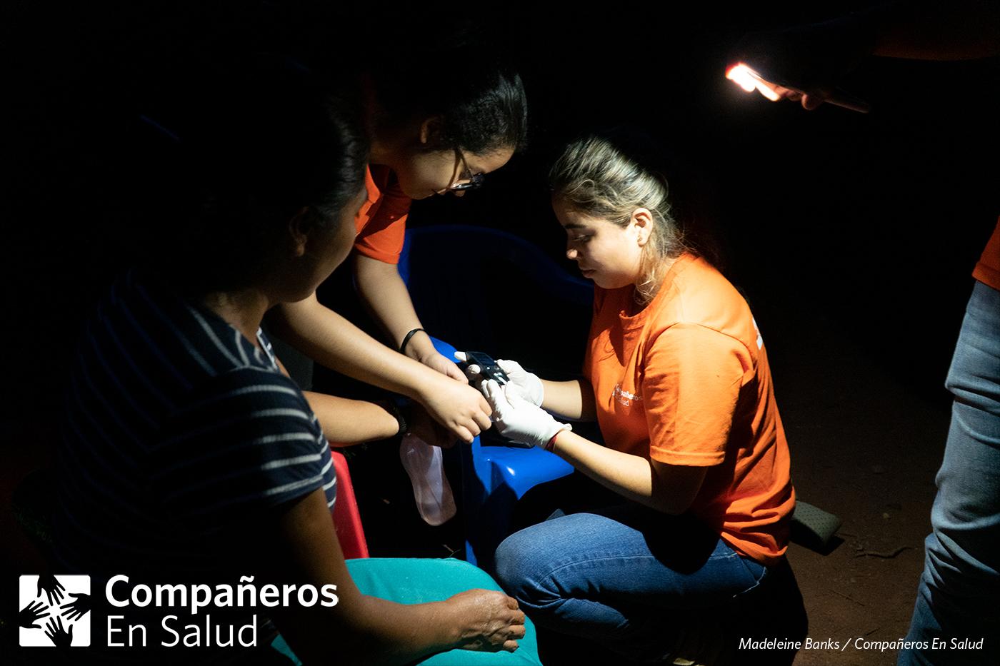 Foto: Karen Yunuen y Gala Limón Saldivar, estudiantes de medicina, miden el nivel de glucosa de doña Rosalinda durante la búsqueda activa en su comunidad.