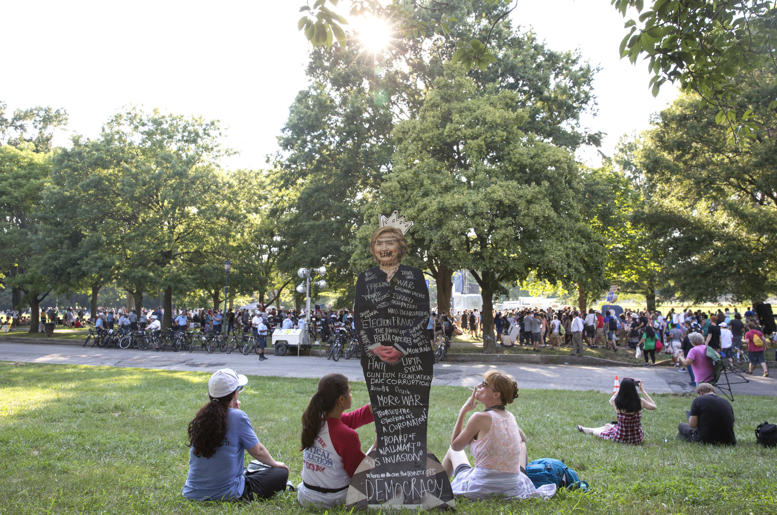 Bernie Sanders supporters hold up a Hillary Clinton cutout while sitting on the grass during the Democratic National Convention in Philadelphia on Tuesday, July 26, 2016.