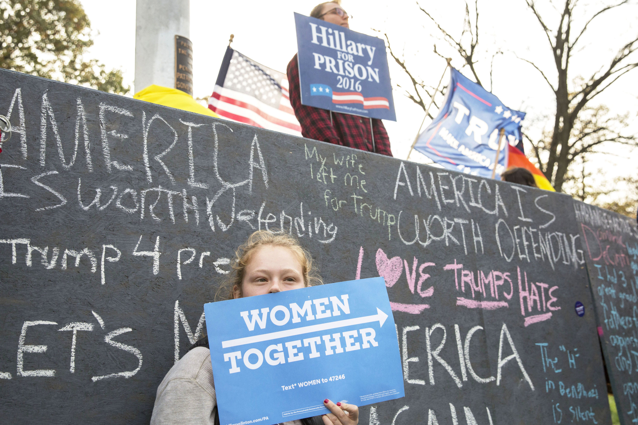 Tessa Sontheimer (junior-community environment and development) holds a sign in support of Hillary Clinton in front of a wall that was built by the Bull-Moose party on Old Main on Tuesday, Nov. 1, 2016.
