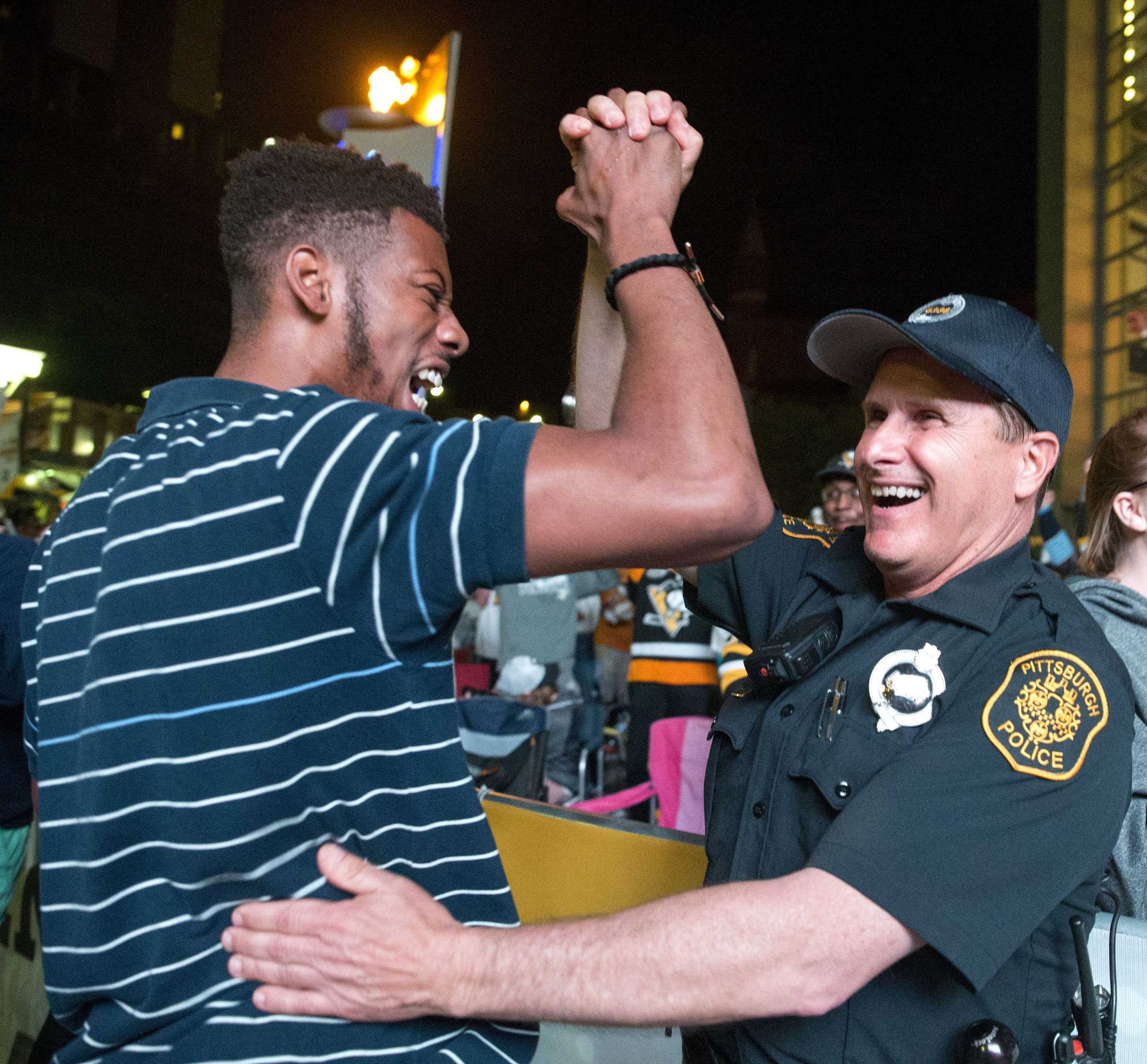 Demtrius Carrington, of Baldwin, celebrates with officer Mike Rosato, of Pittsburgh, after the Penguins scored and lead the game 4-1 against the Predators during Game 2 of the Stanley Cup Finals on Wednesday, May 31, 2017 at PPG Paints Arena.