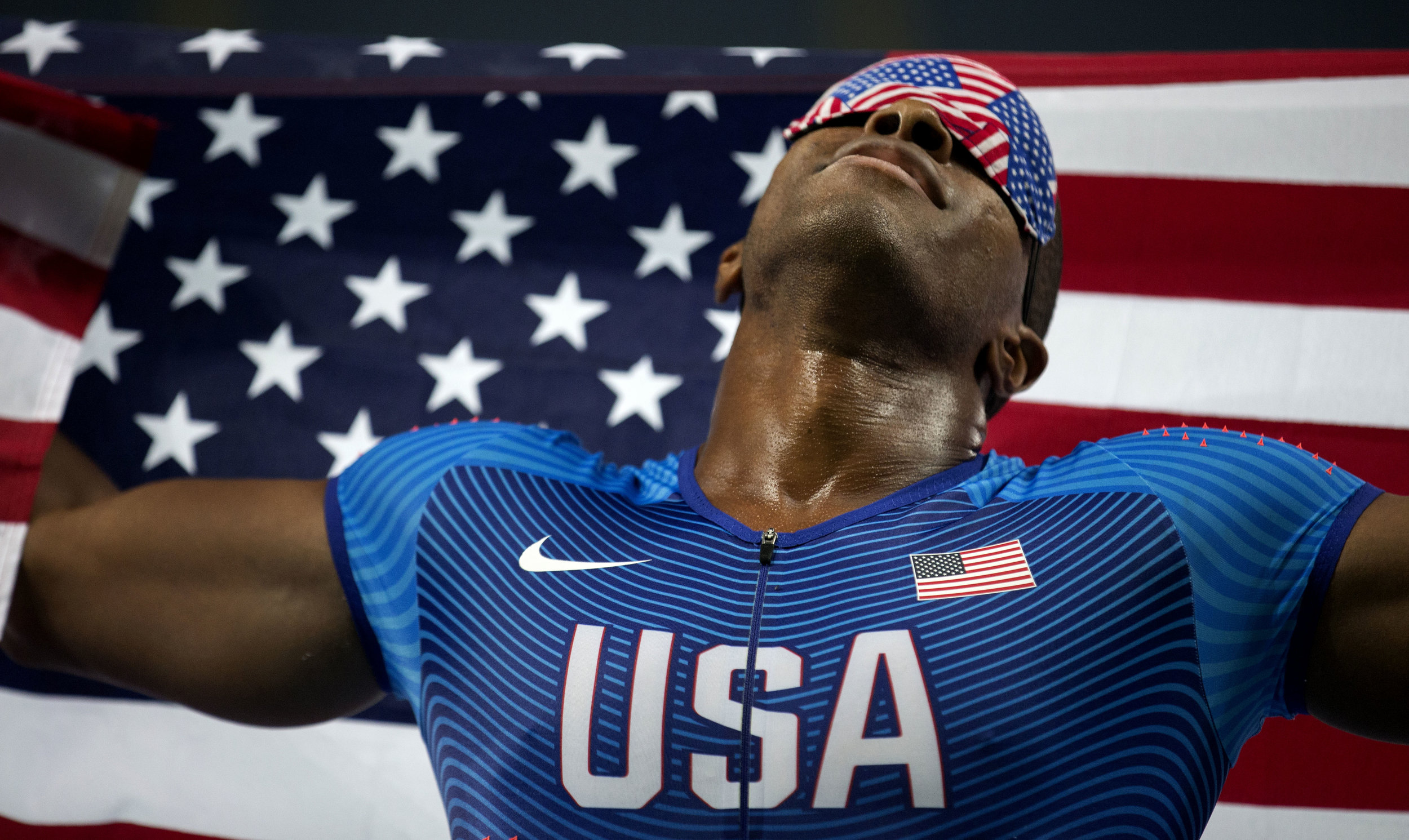 David Brown holds an American flag aloft as he and his sighted guide, Jerome Avery, celebrate Brown's Paralymic record time of 10.99 seconds in the 100 meter dash at the 2016 Paralympic Games at Olympic Stadium in Rio de Janeiro, on Sunday, Sept. 11, 2016.