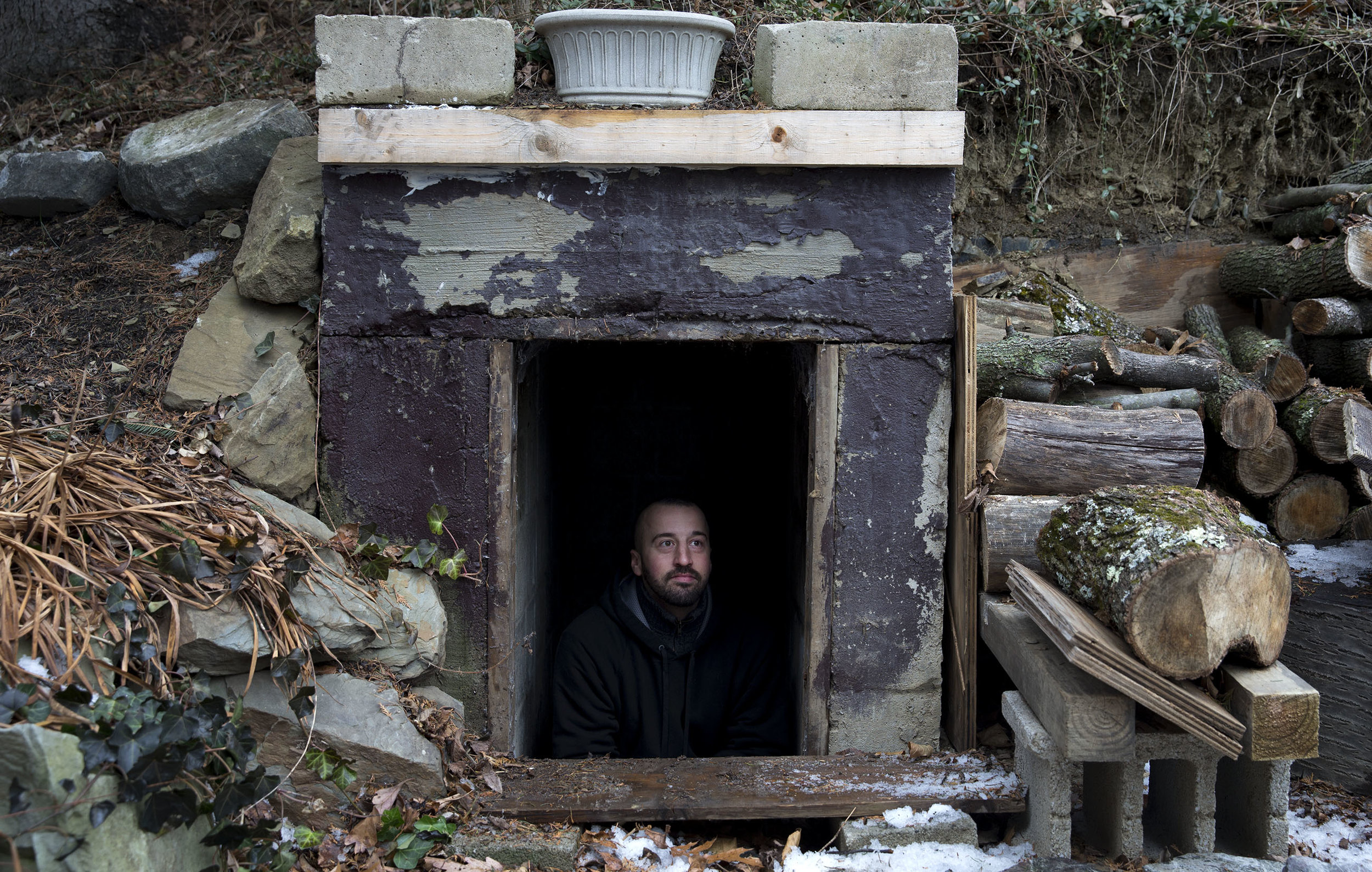 Seth Brokenbek talks with the Post-Gazette while sitting in the entrance of his bunker that was built for shelter into a hillside on his property on Wednesday, Jan. 10, 2018 in Murrysville.