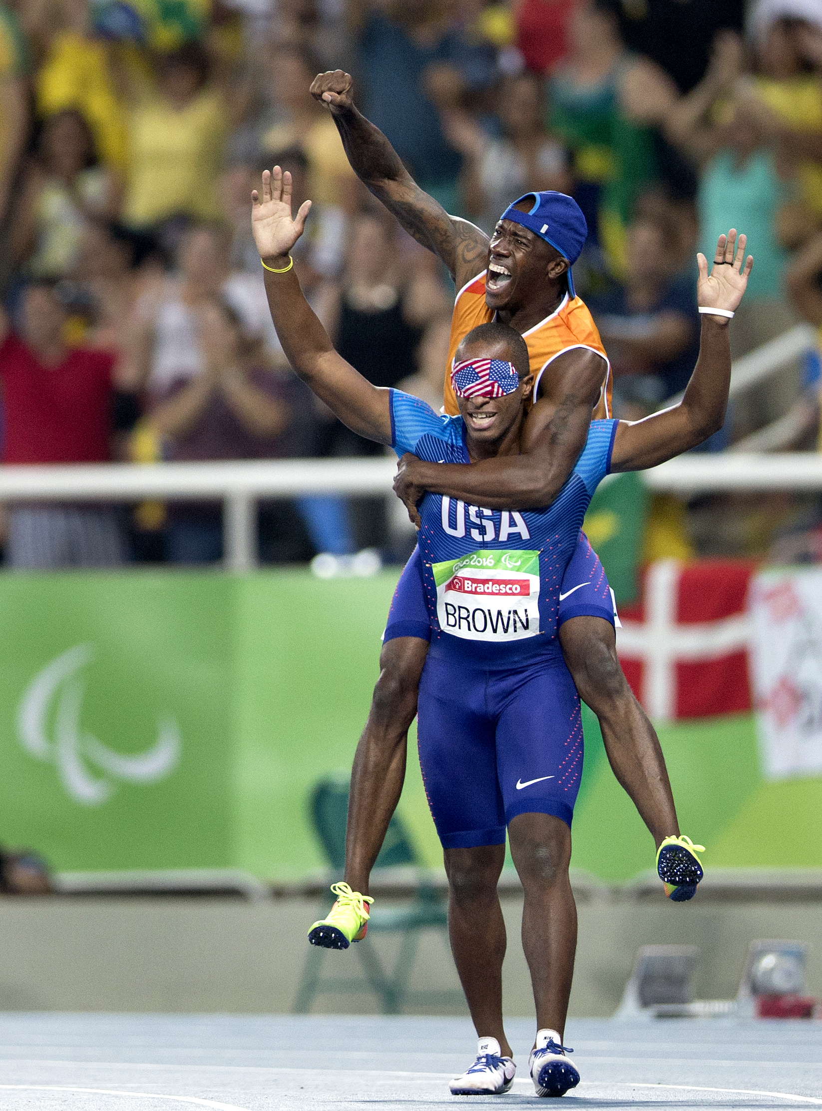 Jerome Avery, David Brown's guide, jumps ontop of Brown's back and celebrate Brown's Paralymic record time of 10.99 seconds in the 100 meter dash at the 2016 Paralympic Games at Olympic Stadium in Rio de Janeiro, on Sunday, Sept. 11, 2016.