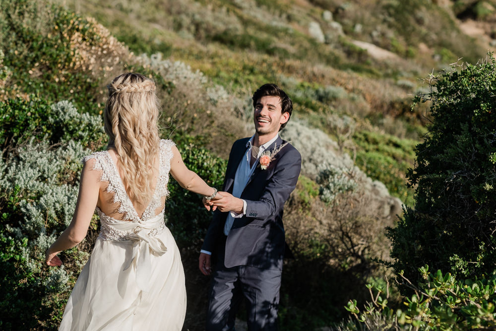 groom-takes-bride-down-to-the-beach-laughing-wedding.jpg