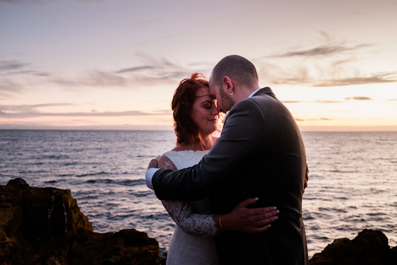 romantic-sunset-wedding-couple-hugging-by-the-ocean-clifftop