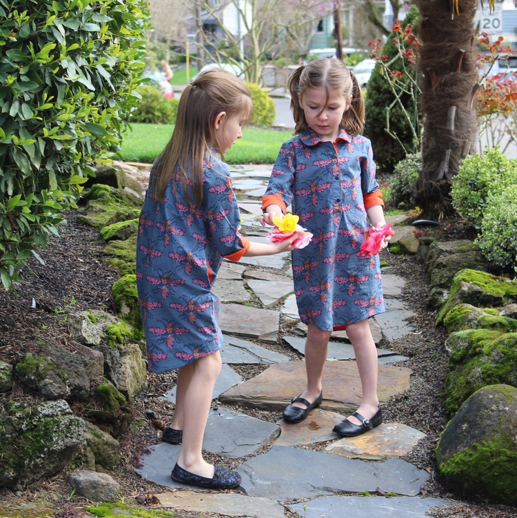nora and etta go for  a walk around the block  in their new bee mine dresses