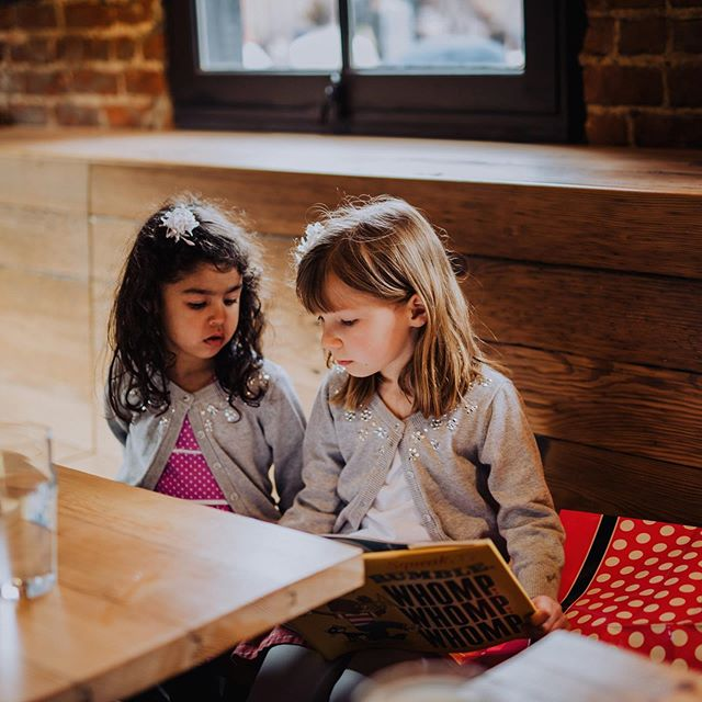rehearsal dinners are far less boring when you have an older cousin who can read to you. | both girls are in @loveauntmaggie creations: maya is in a #librarydress and etta is in the #swingsetskirt both from @oliverands | 📸 @ryansinphoto #theredwoodweddingofmaggieandvictor