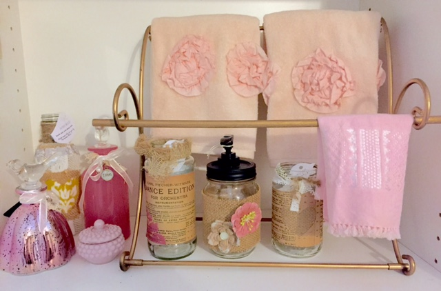 A variety of perfume bottles, jars, soap pumps and a few decorative towels.