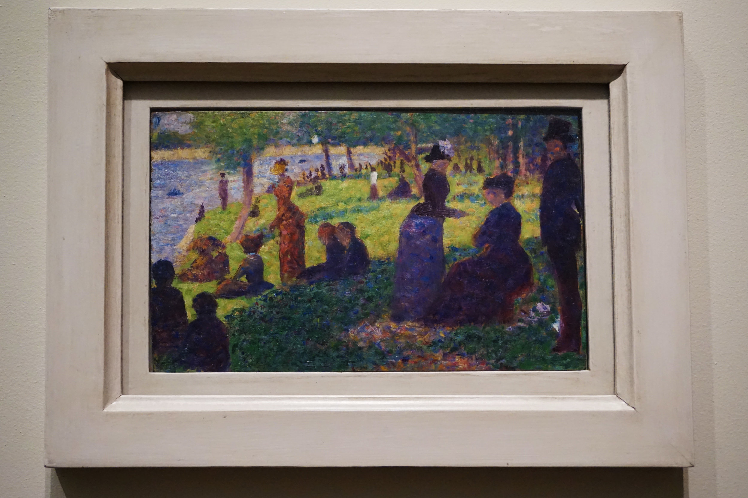 """""""This small oil on a thin wood panel is one of 24 painted studies Georges Seurat made while conceiving the large, celebrated painting  A Sunday on La Grande Jatte  ... Although at first the panel seems close to the larger canvas, its 20 or more figures have little to do with the final composition. The trio at right, for example, with the elderly seated figure, was completely rethought in the final composition, in which a man in a top hat and a woman walking a monkey convey a sense of grand solemnity and wry humor—a sophisticated irony that is completely absent in the clumsily positioned figures of the oil panel."""""""