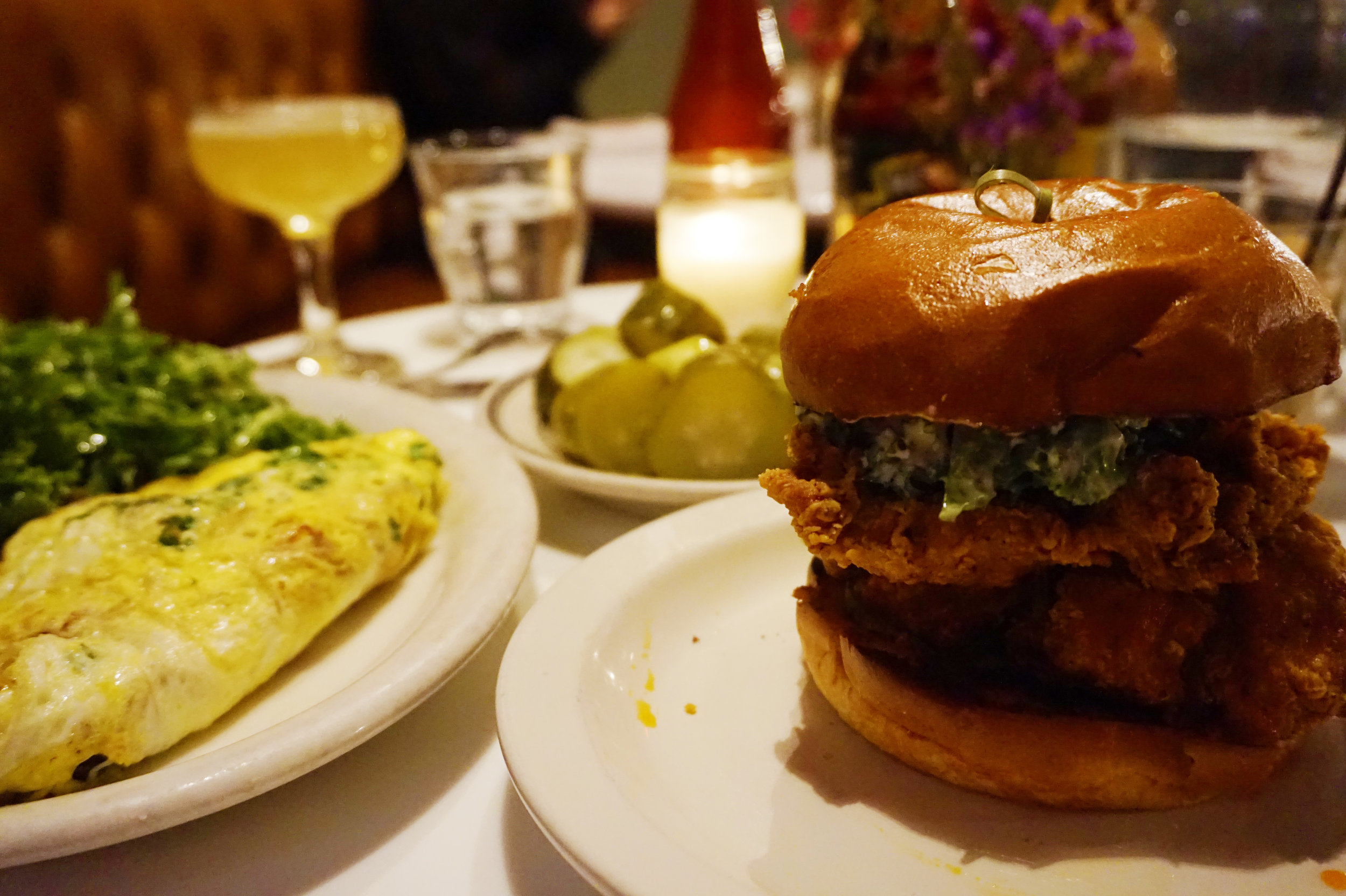 Fried chicken sandwich, goat cheese and kale omelette, and a side of pickles