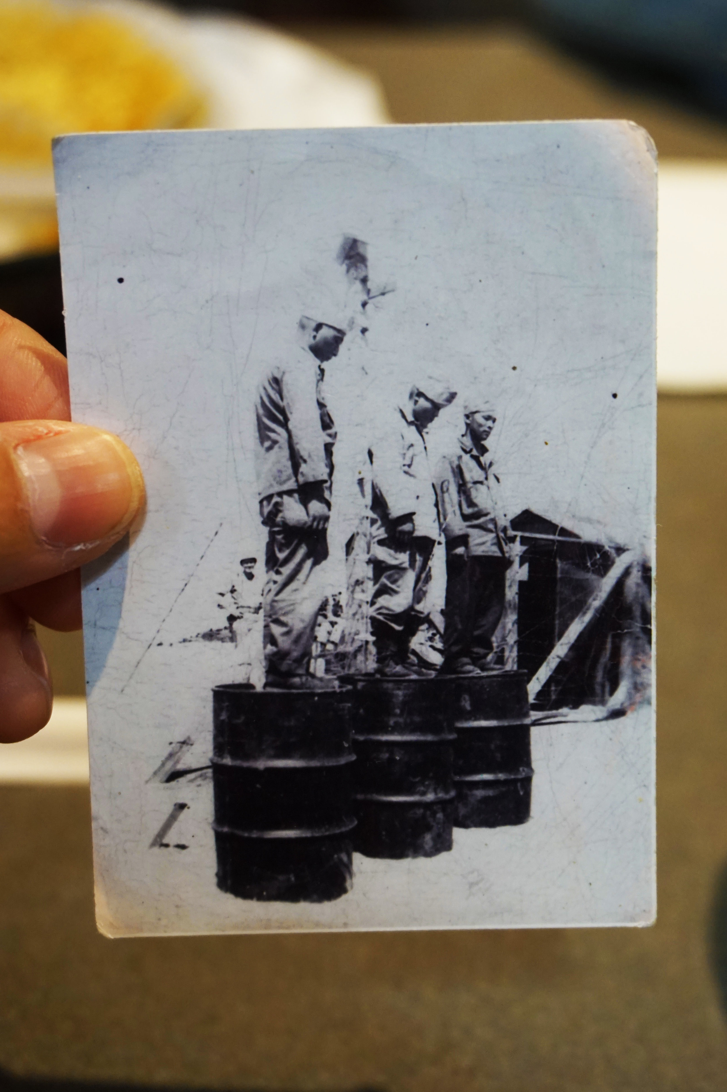 A picture George kept in his wallet of Japanese soldiers standing on oil barrels