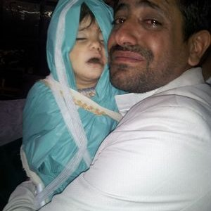 Ibrahim Abdulkareem holding his one year old daughter, Zainab, for the last time before her burial.