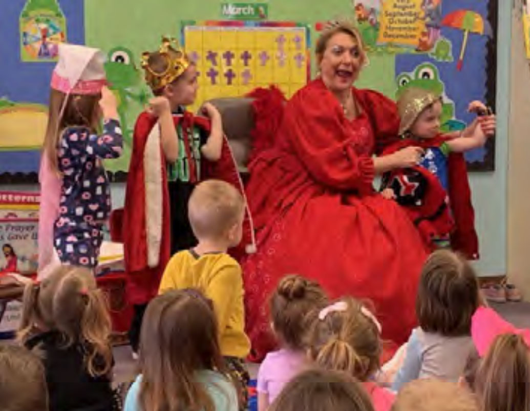 "The ""Queen of Hearts"" acts out a story with the children. Oh my…..what big muscles the knight has!"