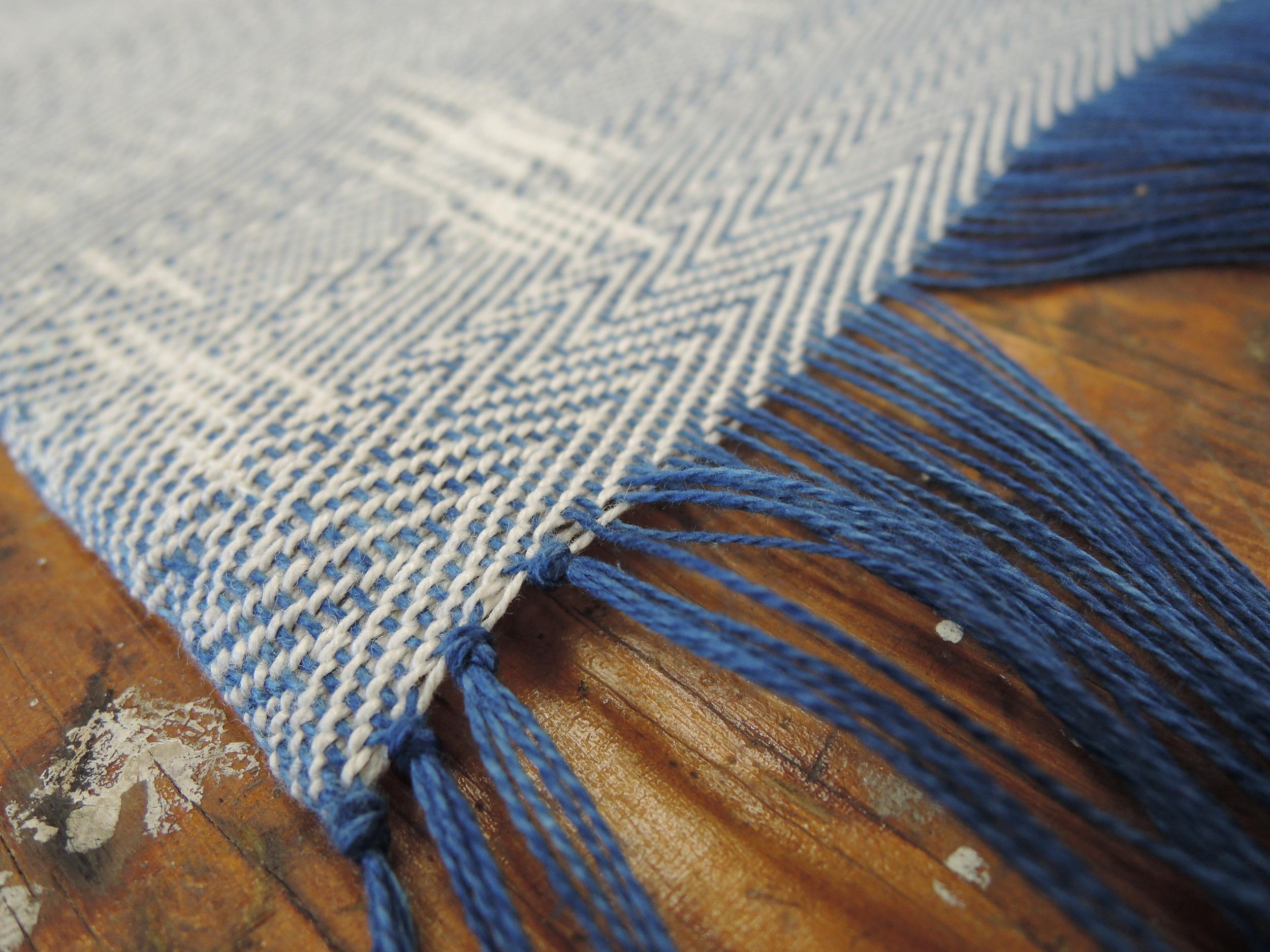 Carefully tying knots to finish the edges.