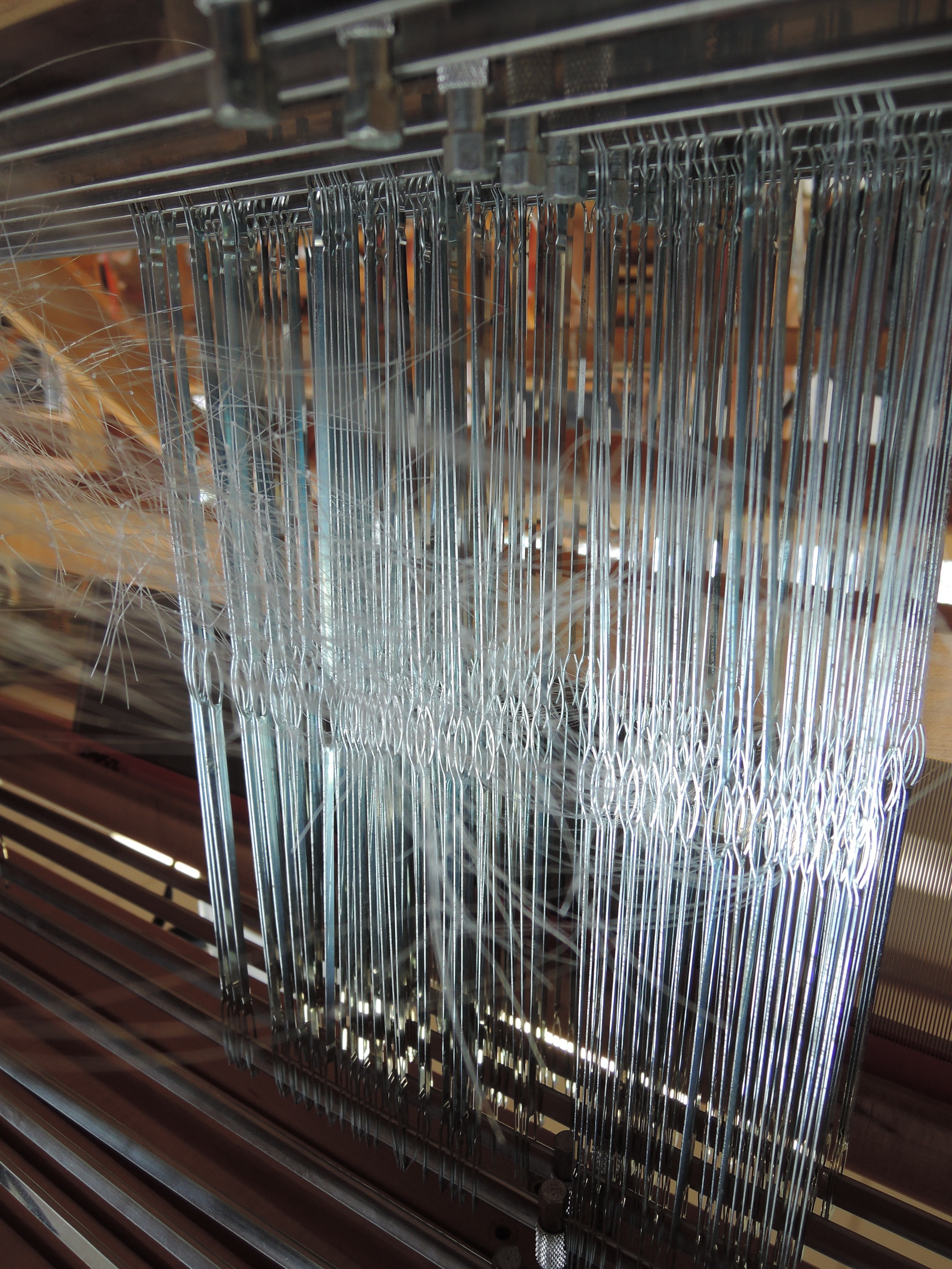 The threads are nearly invisible, but they're all neatly threaded through each of those heddles.