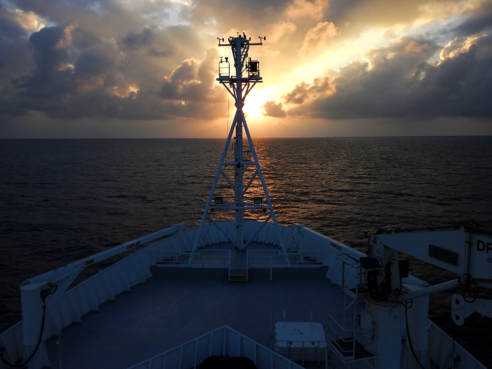 The Sun sets on our voyage. Note the majestic lone booby atop the mast. Photo: Katie Walters